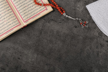 Flat lay composition with Muslim prayer beads, Quran and space for text on grey background