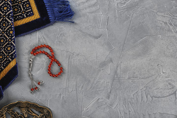 Flat lay composition with Muslim prayer beads, rug and space for text on grey background