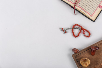 Flat lay composition with Muslim prayer beads, Quran and space for text on white background