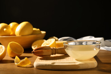 Composition with lemon juice and wooden reamer on table