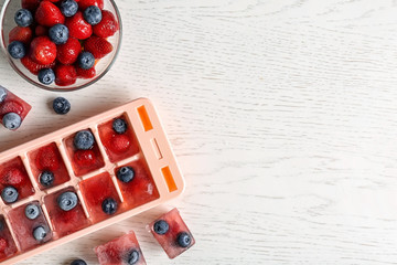Flat lay composition with ice cube tray and berries on wooden background. Space for text