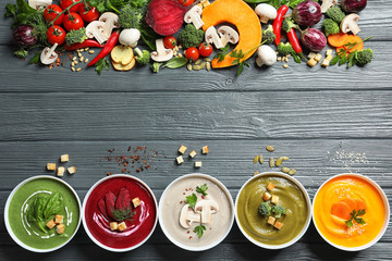 Various cream soups, ingredients and space for text on wooden background, flat lay. Healthy food