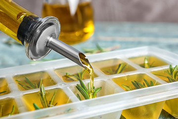 Pouring olive oil into ice cube tray with rosemary on table, closeup