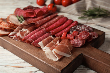 Cutting board with different sliced meat products served on table