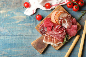 Cutting board with different sliced meat products on wooden background, flat lay. Space for text