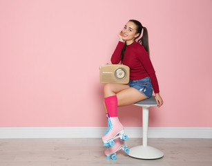 Young woman with roller skates and retro radio sitting on chair near color wall. Space for text