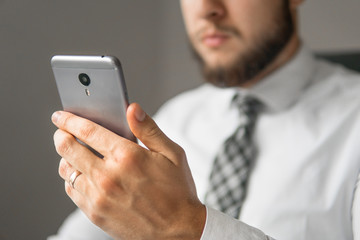 Holding smartphone in hand. Young bearded businessman. Office work with a laptop. Light background. Financial business. Businessman work with computer on table in office work.