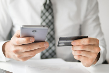 Smartphone and Internet Commerce. Online payments through the phone. Young businessman with a bank credit card in his hands. Payment of goods online. Online trading on the currency exchange.
