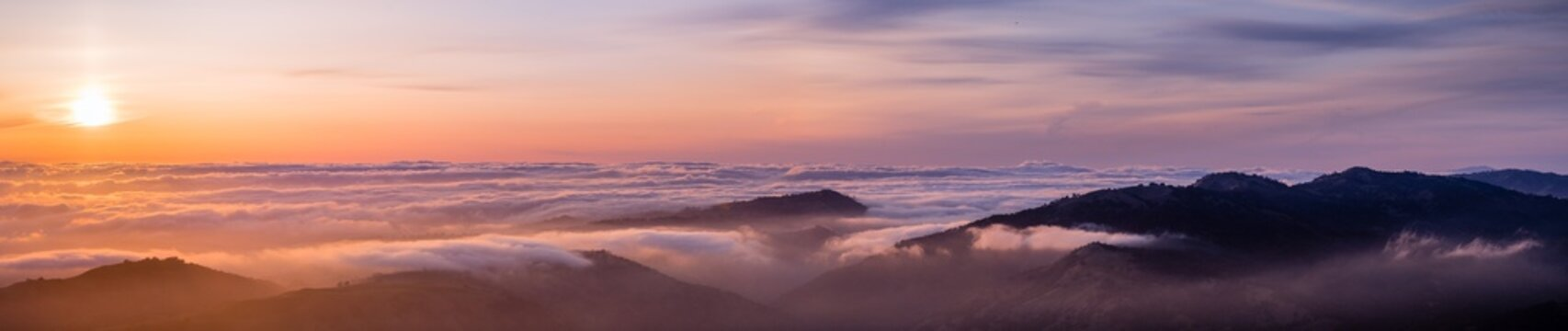 Panoramic view of a sunset over a sea of clouds covering south San Francisco bay area; mountain ridges in the foreground; view from Mt Hamilton, San Jose, Santa Clara county; California