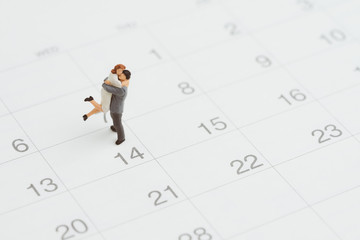 Miniature people figure lovely couple holding each other standing on 14th Feb calendar as wedding anniversary or Valentine's day celebration