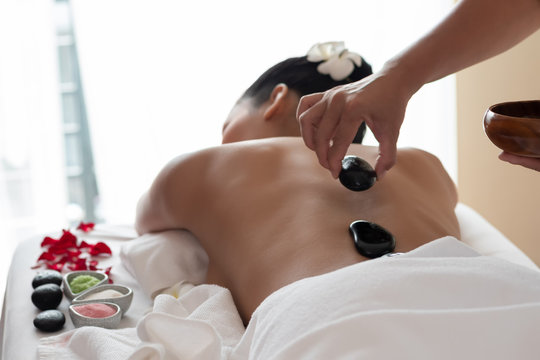 Young asian woman lying relaxing getting hot stone massage in spa salon. Beauty treatment concept