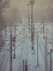 Foggy evening over empty train tracks in winter time