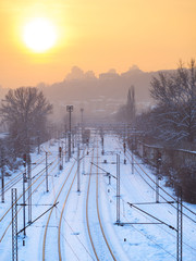 Train tracks in winter time near industrial part of the city