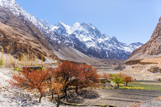 Beautiful autumn scene along Karakorum highway with layers of snow mountains and blue sky background