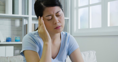 young woman suffering from severe headache.
