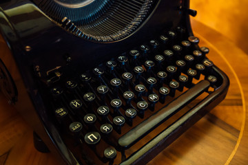 Old black typewriter with Russian Cyrillic letters on  wooden table, close up