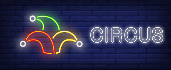 Circus neon text with jester hat. Circus performance advertisement design. Night bright neon sign, colorful billboard, light banner. Vector illustration in neon style. Wall mural