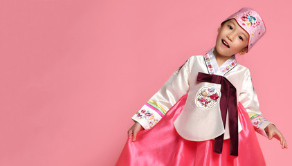 Korean little baby girl in traditional silk dress celebrate new year 2019 on pink background