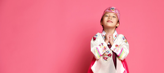 Korean little baby girl in traditional silk dress celebrate new year 2019 on pink background praying