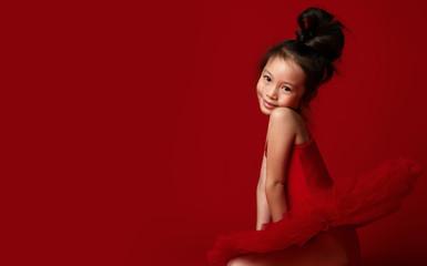 Cute little girl ballerina in beautiful dress is dancing on red