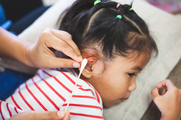 Parent helping her child perform first aid ear injury after she has been an accident