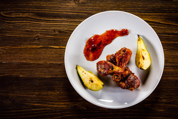 Grilled chicken drumsticks with pear on wooden background
