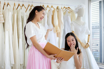 Beautiful bride getting dressed by her best friend in her wedding day and choosing a wedding dress in the shop and the shop assistant is helping her