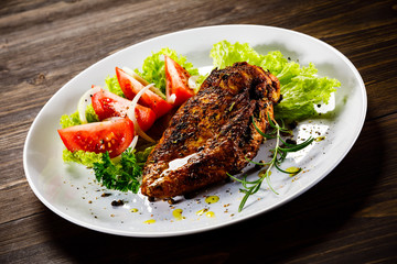 Grilled chicken fillet and vegetables on wooden background