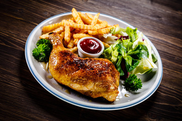Roasted chicken leg with french fries and vegetable salad on wooden background