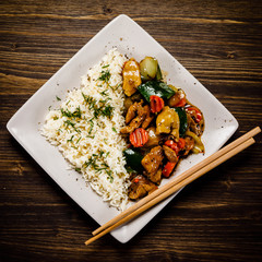Grilled meat, white rice and vegetables on wooden table