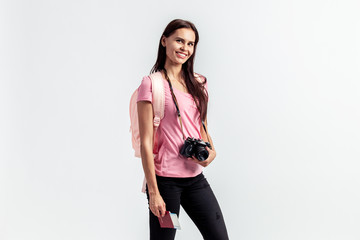 Smiling girl with a backpack on her shoulders dressed in pink t-