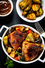 Grilled chicken legs with baked potatoes and vegetable salad on black stone plate