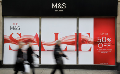 Shoppers walk past sale signs at Marks and Spencer on Oxford Street in London