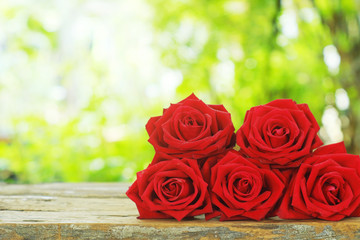 Group of lovely blooming red color rose flower on wood table with blur green garden background, sweet valentine present concept
