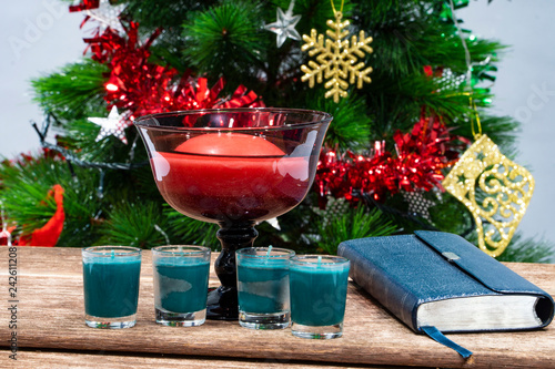 Candles are prepared on a table in front of a Christmas tree