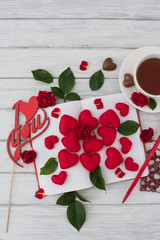 Valentines day. Notebook on a white wooden table with red hearts. Romantic morning on the day of lovers. Top view