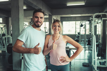 People sport couple concept in fitness gym are giving thumbs up for symbol good health., Portrait of couple in sportswear are exercising in gym., Healthy and sport concept.
