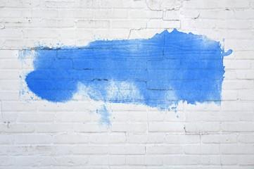 Weiße Backsteinwand mit blauer Farbfläche