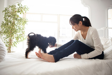 ベッドの上で愛犬と戯れる女性