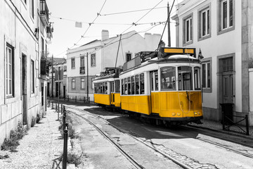 Yellow vintage trams on old streets of Lisbon, Alfama, Portugal, popular touristic attraction and destination. Black and white picture with a coloured tram.