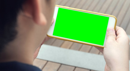 Teen holding a smartphone in the hands of a green screen.