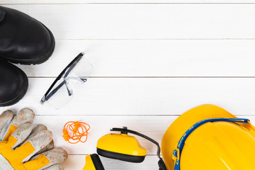 Banner image of construction safety equipment flat lay on white wooden.