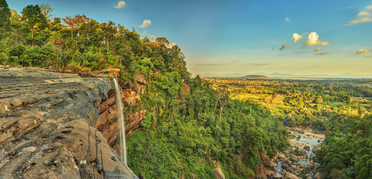 Beautiful waterfall flowing from the cliff in the tropical jungles panoramic top view