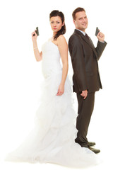 Groom and bride in wedding outfit holding guns