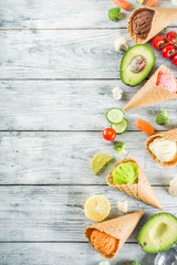Trendy vegan food, summer healthy dessert concept, colorful diet vegetable ice cream with avocado, cucumber, tomato, beet, carrot, broccoli, cauliflower. Frozen veggie smoothie, wooden background