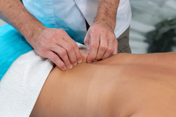 Osteopath massages the patient on her back. Tightening the skin.