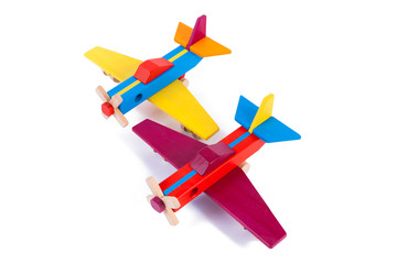 Photo of two wooden multi-colored aircraft from beech. Toy wood retro planes on a white background isolated
