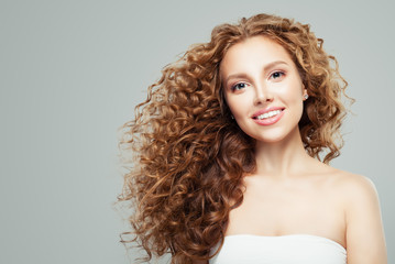 Fashion beauty portrait of young redhead woman with long healthy curly hair gray background