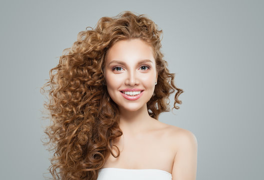 Happy redhead woman with long healthy curly hair. Cute female face