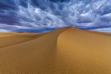 Cloudy sky over sand dunes in the desert